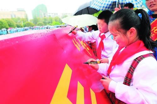 图为献花仪式上大家争相在红布上签名,表示要牢记使命不忘革命优秀传统。 记者唐侃 摄