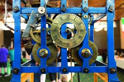 一台近2米高的古老机械钟表装在铁架子上,上面是大小不一的齿轮