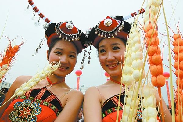 文化节上的仫佬族少女手捧手工制作的稻穗,以示对食物的尊敬.
