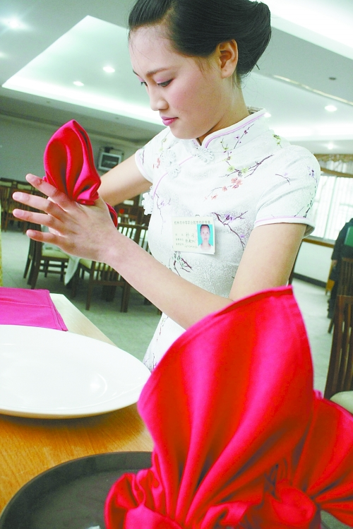 选手在制作餐巾杯花;