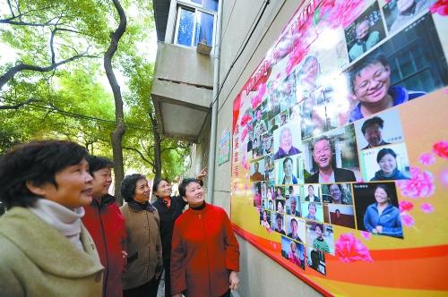"""南昌市青云谱区三店街道南苑社区的居民们在参观小区里的""""笑脸墙"""".图片"""